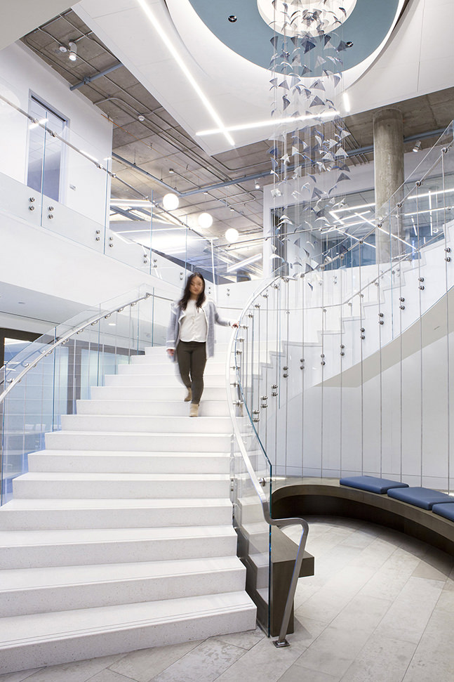 A girl walks down the stairs next to Pacific a hanging metal sculpture, corporate art by Talley Fisher.