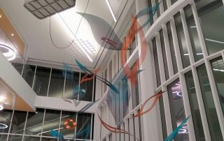 An art rigger in an aerial lift installs cables to a grid suspending the atrium sculpture.