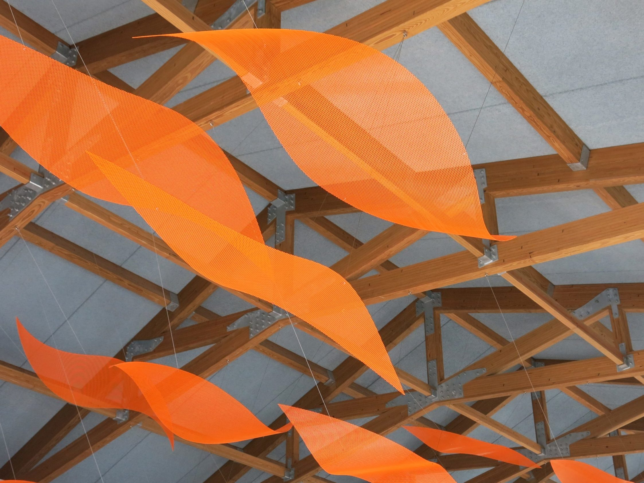 Orange petals of the suspended sculpture by Talley Fisher in Aurora Health and Wellness Center.