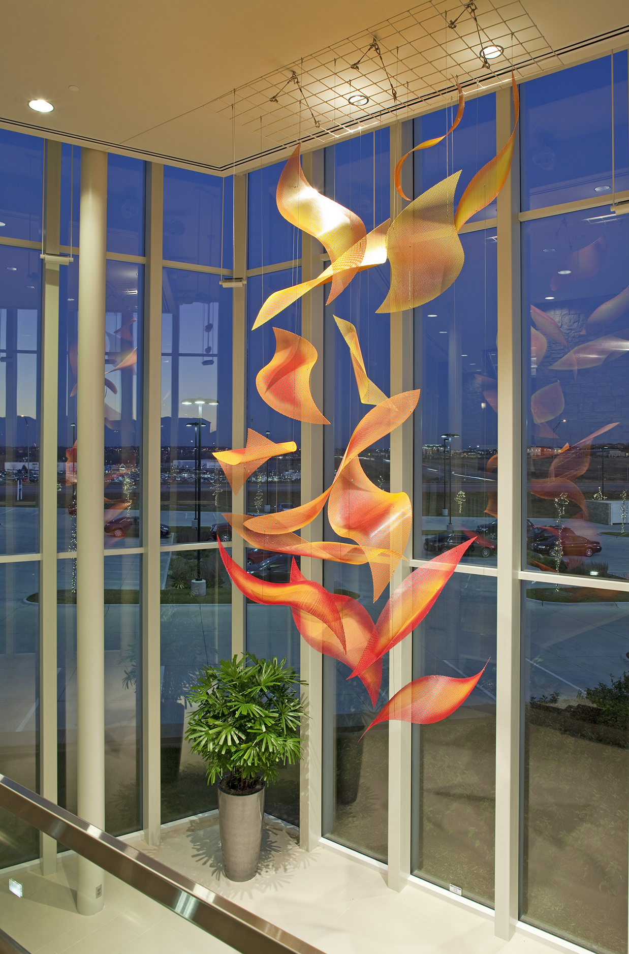 Sunrise Cascade suspended contemporary sculpture by Talley Fisher in a glass atrium at dusk.
