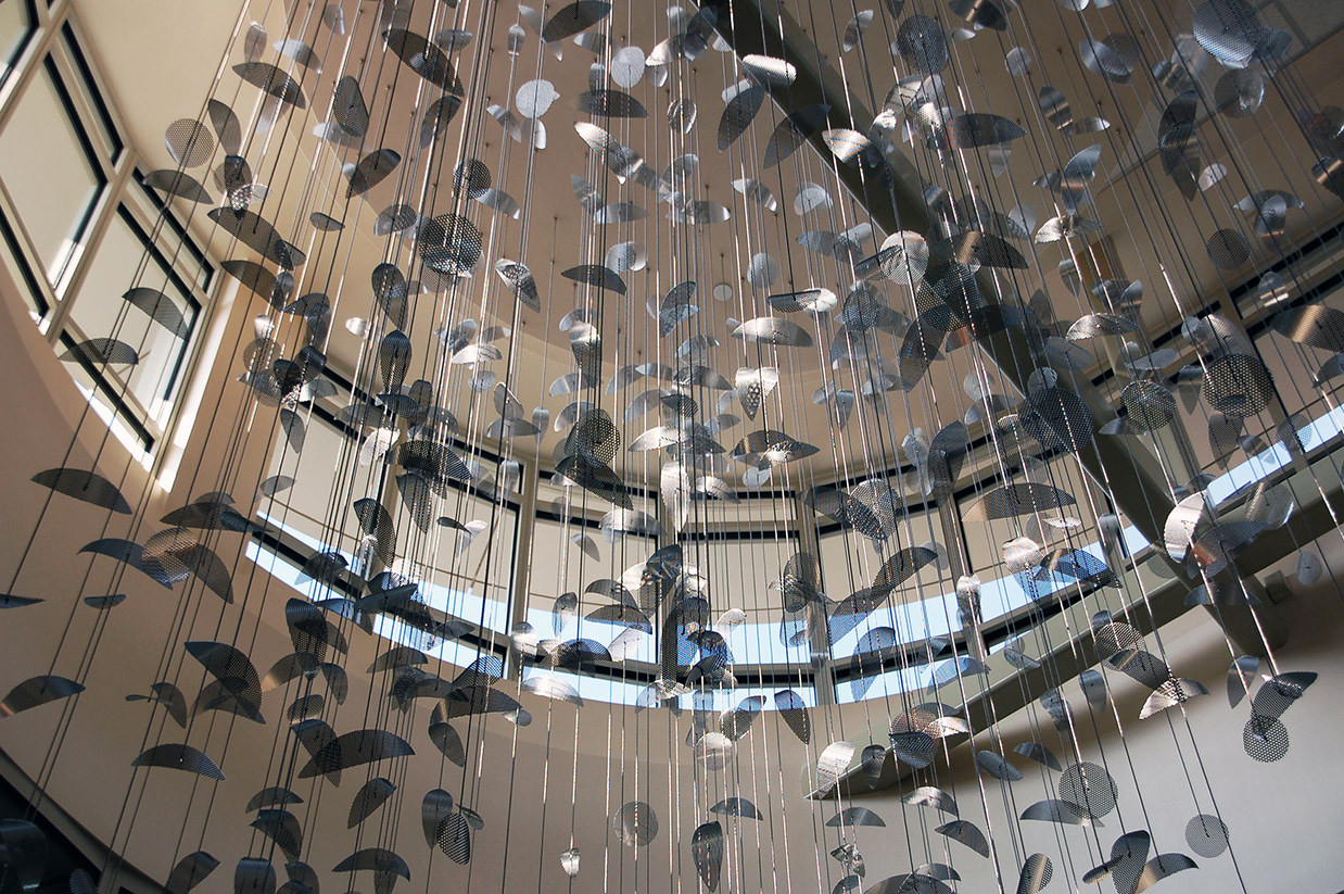 Constellation II, silver hanging mobile art, is illuminated by sunlight.