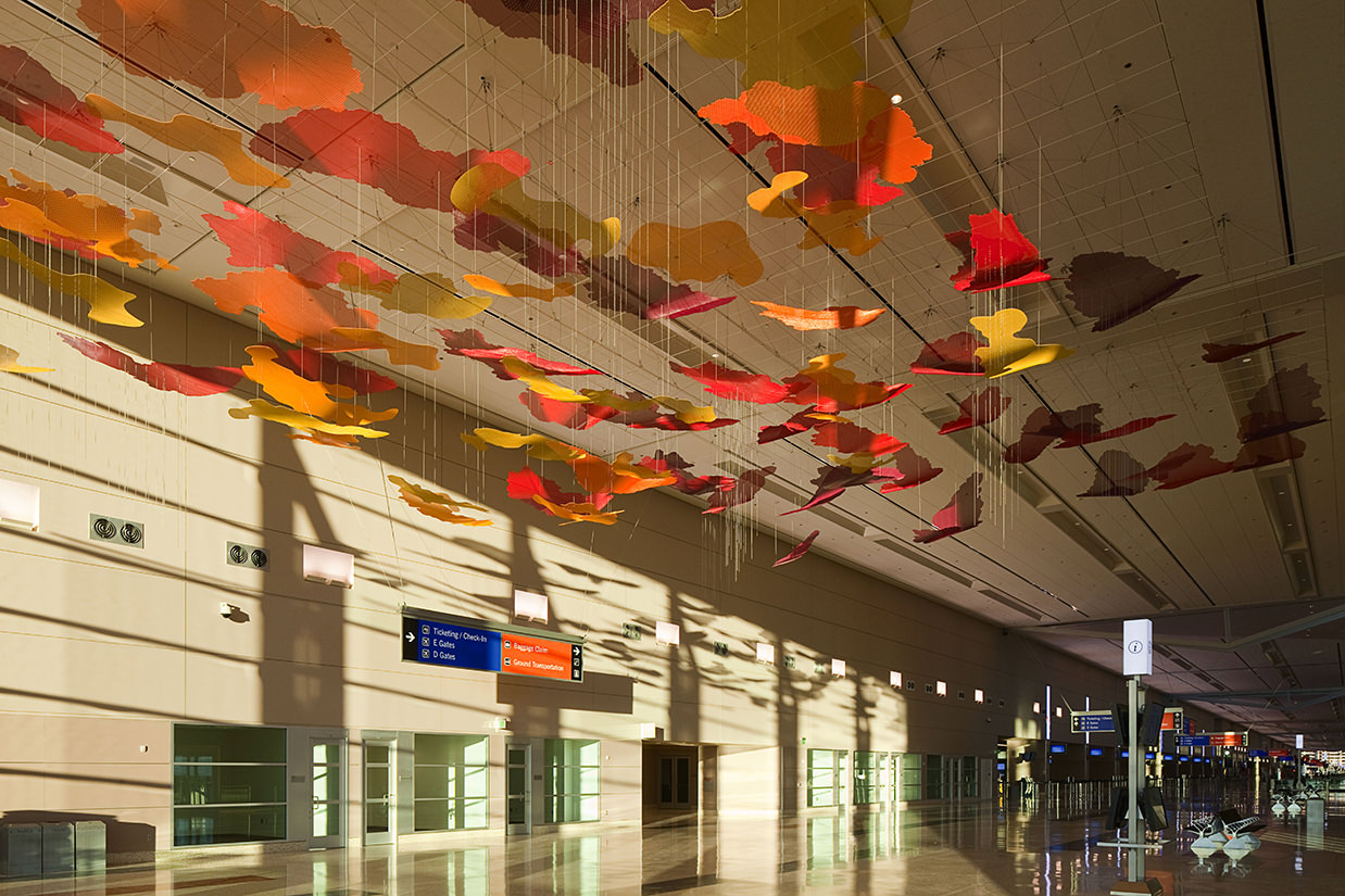Sun illuminating the clouds in Desert Sunrise, Talley Fisher's airport art sculpture in McCarran International Airport