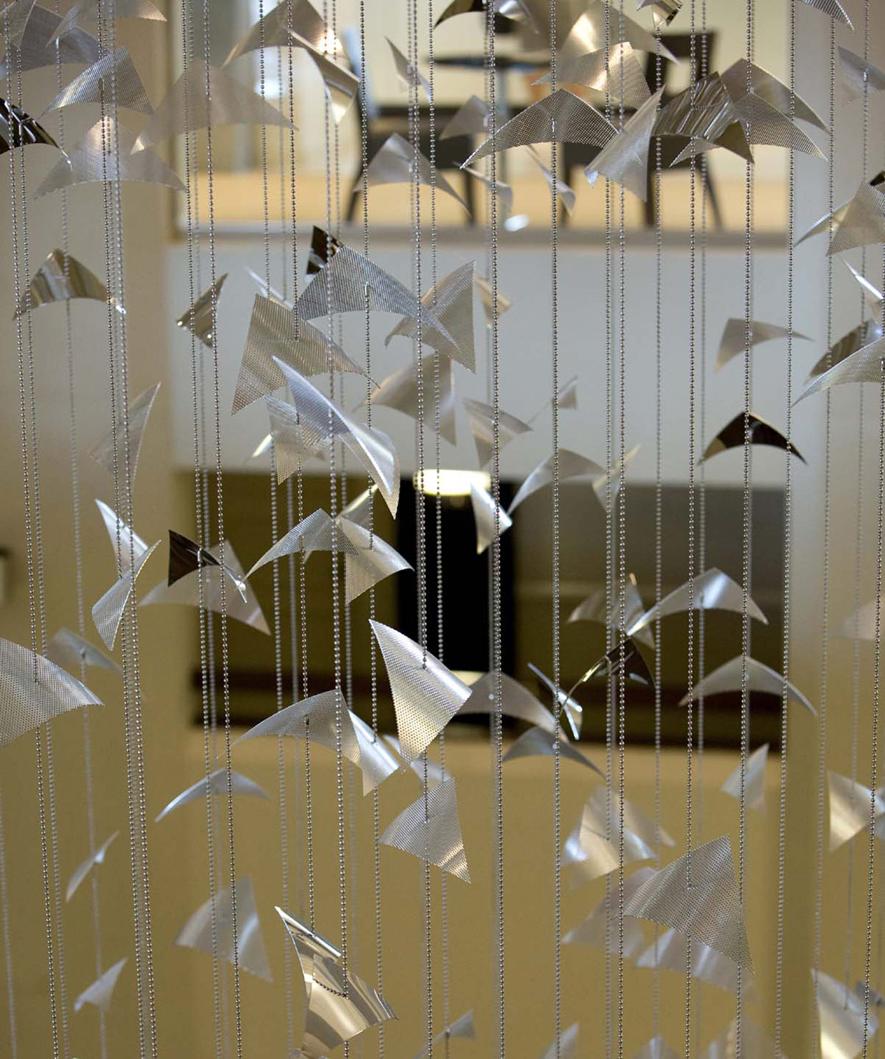 Silver elements of Migration, suspended sculpture by Talley Fisher