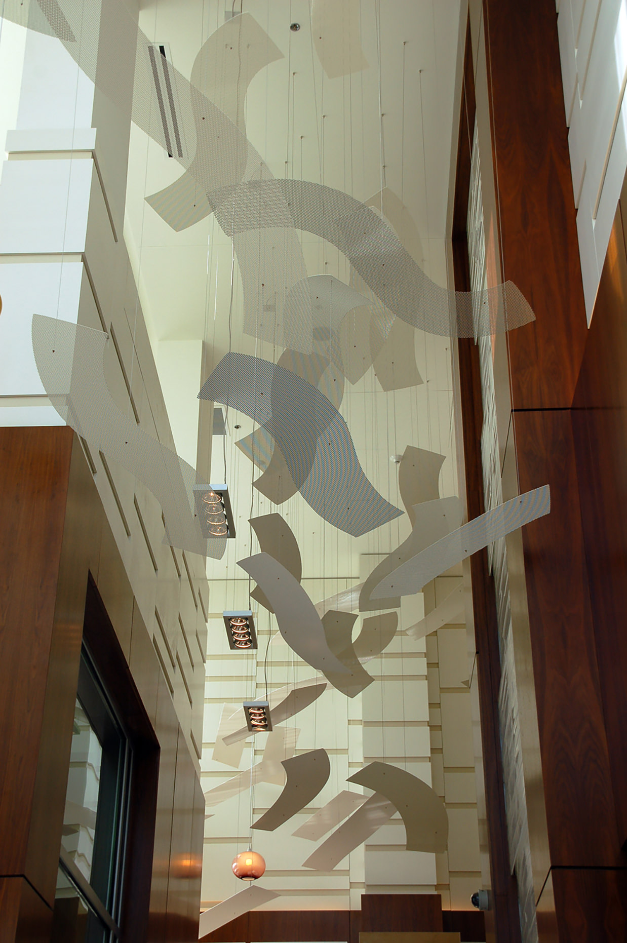 Talley Fisher's Rhythm of the Rails suspended art installation in a wood-lined lobby.