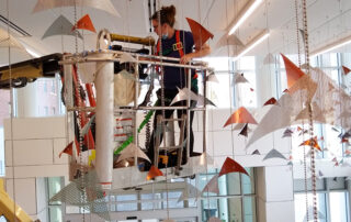 Artist Talley Fisher installing hanging elements of Flight Over the Susquehanna.